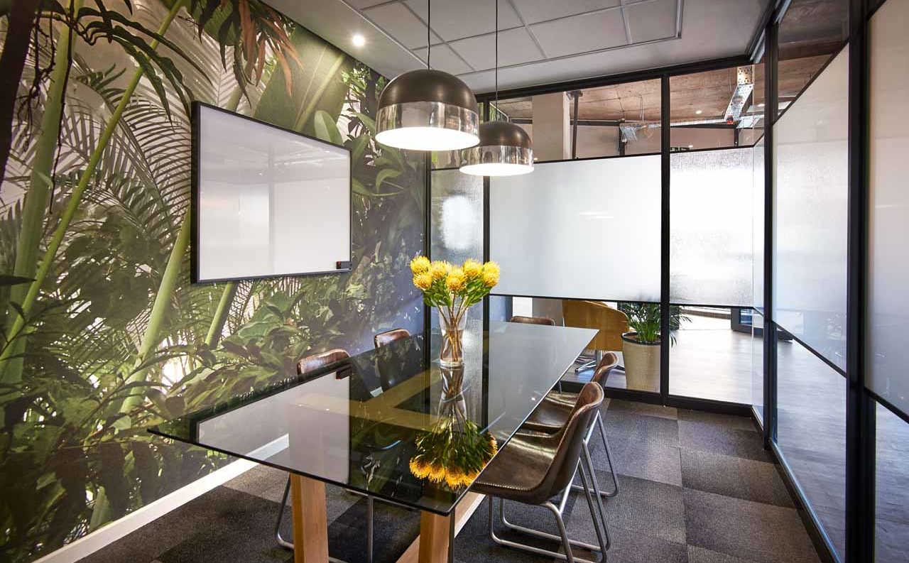 A modern meeting room with stylish wallpaper, a glass table and leather chairs at a branch of The Workspace
